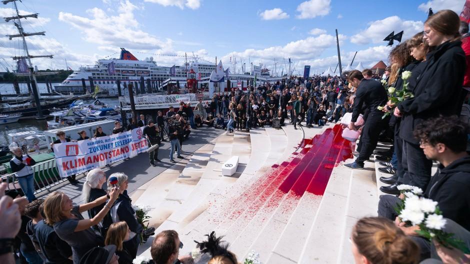 Aktivisten der Gruppierung Extinction Rebellion schütten während der Hamburg Cruise Days eine rote Flüssigkeit, die Blut darstellen soll, auf die Treppen.
