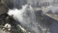 Die Feuerwehrleute versuchen, das Feuer zu löschen, das durch einen Flugzeugabsturz in Karatschi, verursacht wurde.