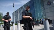 Die Fahne auf Halbmast: Britische Polizeibeamte bewachen das Hauptquartier der Polizei von Manchester.