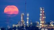 Ein roter Vollmond hinter der Erdölraffinerie im Hamburger Hafen