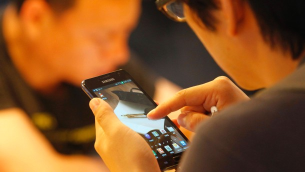 People try out the Galaxy smartphones displayed in a store at the headquarters of Samsung Electronics in Seoul