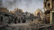 Ein vergifteter Sieg: Fliehende Zivilisten passieren die schwer beschädigte Al-Nuri Moschee in Mossul.