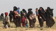 Frauen fliehen mit ihren Kindern aus einem vom IS gehaltenen, umkämpften Dorf im Osten Syriens.