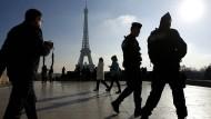 Polizisten patrouillieren vor dem Eiffelturm.