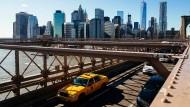 Ein Taxi fährt vor der Skyline von Lower Manhattan über die Brooklyn Bridge in New York.