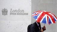 Ein britischer Regenschirm läuft an der Londoner Börse vorbei.