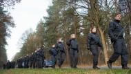 Polizisten suchen nach Spuren in einem Wald an einer Landstraße bei Celle.