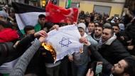 Teilnehmer einer Demonstration verbrennen Mitte Dezember eine selbstgemalte Fahne mit einem Davidstern im Berliner Stadtteil Neukölln.