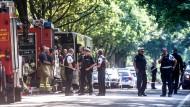 Einsatzkräfte stehen vor einem Bus (halb verdeckt) im Lübecker Stadtteil Kücknitz, in dem ein Fahrgast Mitreisende mit einem Messer attackiert hatte.