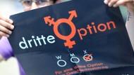 Eine intersexuelle Person hält ein Plakat für ein drittes Geschlecht hoch.