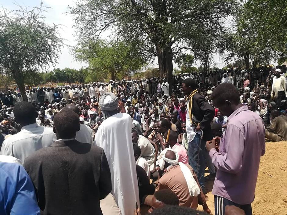 Anwohner versammeln sich Ende Juli nach einem Angriff auf das Dorf Masteri zu einer Massenbeerdigung.