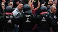 In Bedrängnis: Polizisten stellen sich am Montagabend in Chemnitz dem braunen Mob entgegen.