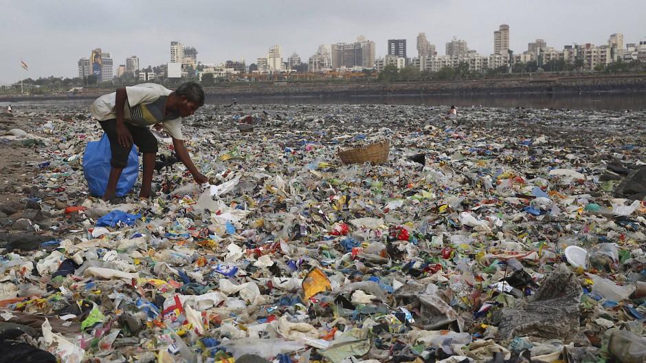 Ein Mann sammelt Plastik und andere wiederverwertbare Materialen an der von Plastiktüten und sonstigen Müll übersäten Küste des Arabisches Meeres.