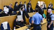 Nicht das Gesicht verlieren: Vor Beginn des Prozesses am Frankfurter Landgericht um eine mutmaßliche Teufelsaustreibung schützen Anwälte ihre koreanischen Mandanten vor Porträtaufnahmen.