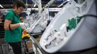 Eine Vorwerk-Mitarbeiterin schraubt in einer Fabrik in Frankreich an einen Thermomix.