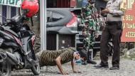 Ungewöhnliche Bestrafung: Wer in Indonesien von der Polizei ohne Maske erwischt wird, muss sich umgehend körperlich ertüchtigen.