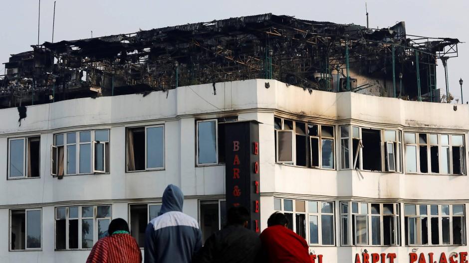 Passanten betrachten das ausgebrannte Stockwerk des Hotels in Neu-Delhi.