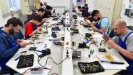 Junge Flüchtlinge arbeiten in einer Ausbildungswerkstatt der Deutschen Bahn, damit sie eine Ausbildung zum Elektriker beginnen können.