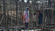 Flüchtlinge in den Überresten von Zelten im abgebrannten Lager auf Lesbos