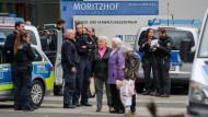 Nach einer Bombendrohung am 8. November 2018 sprechen Polizeibeamte mit Passanten vor dem Gebäudekomplex Moritzhof in Chemnitz, in dem sich auch das Jugendamt befindet.