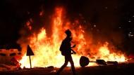 Ein Demonstrant geht an einer brennenden Barrikade vorbei.