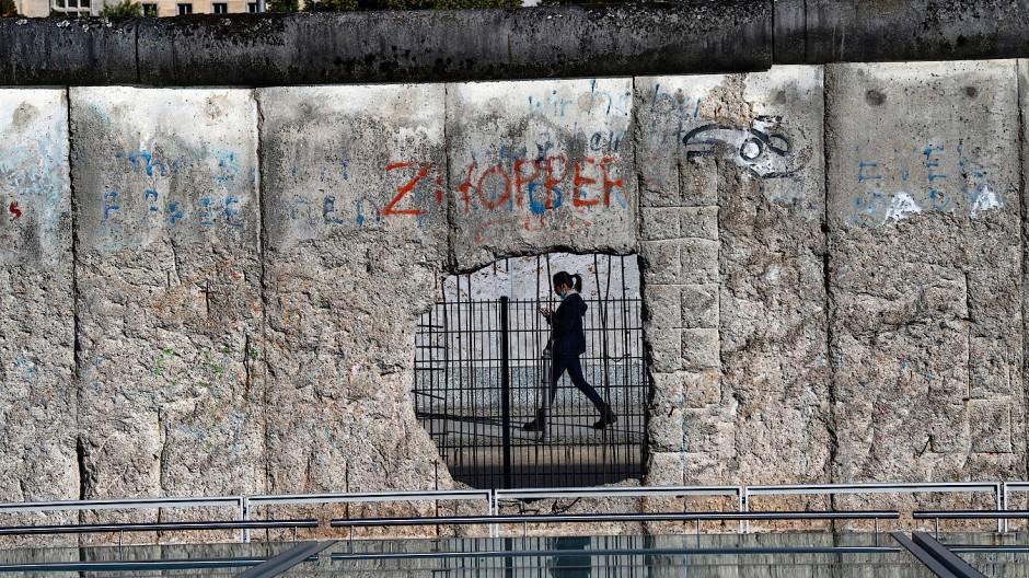 Eine Frau ist durch ein Loch der ehemaligen Grenzmauer an der Niederkirchnerstraße zu sehen, Berlin, 28. September 2020.