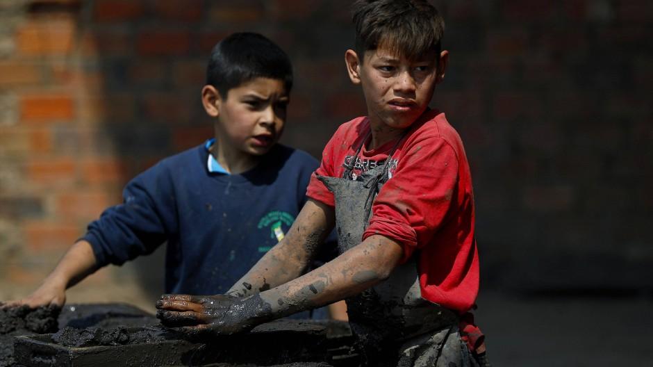 Ein elf Jahre und ein 13 Jahre alter Junge arbeiten in einem Lehmziegelwerk in Tobati in Paraguay.