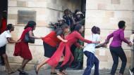 """""""Lauft so schnell ihr könnt!"""": Zivilisten bringen sich am Dienstag in Sicherheit, während der Angriff auf das Hotel in Nairobi im Gange ist."""