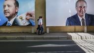 Zwei Menschen gehen fünf Tage vor den Parlaments- und Präsidentschaftswahlen in der Türkei an überdimensionalen Wahlplakaten vorbei.