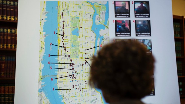 A woman looks at a map showing where eight members belonging to a New York-based cell of a global cyber criminal organization withdrew money from ATM machines, during a news conference in New York