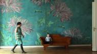 Rosefarbenes Blütenmeer auf blauem Grund: Die Wandbespannung verwandelt die hohen Wände der Altbauwohnung in einen verwunschenen Garten.