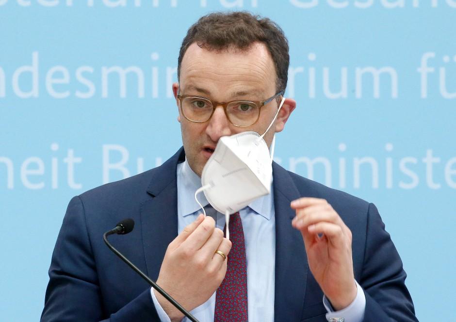 Jens Spahn nimmt seine Maske ab.