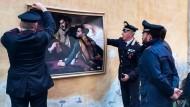 Von den Herren auf dem Bild geht Gefahr aus: Polizisten in Rom entfernen ein Gemälde das Matteo Salvini und Luigi Di Maio zeigt.