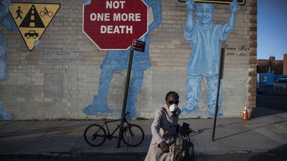 Eine Frau mit Maske überquert die Straße im New Yorker Stadtteil Brooklyn. Im Hintergrund ist ein Stoppschild auf die Wand gemalt: Nicht ein Toter mehr!