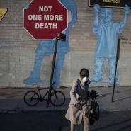 """Eine Frau mit Maske überquert die Straße im New Yorker Stadtteil Brooklyn. Im Hintergrund ist ein Stoppschild auf die Wand gemalt: """"Nicht ein Toter mehr!"""""""