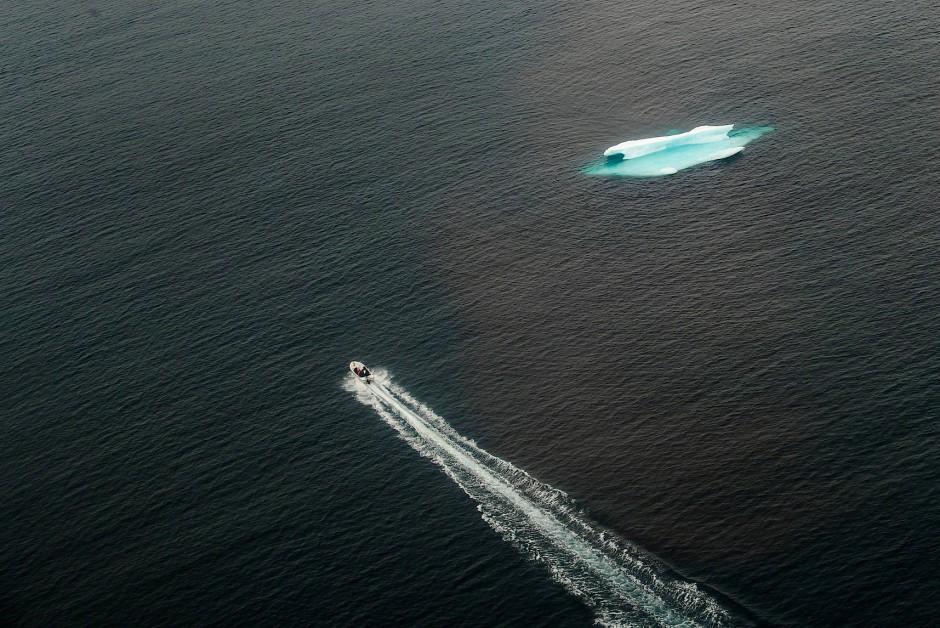 Ein kleines Motorboot fährt an einem Eisberg vor der Küste von Tasiilaq vorbei.