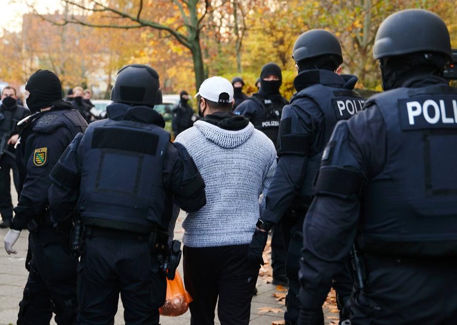 Polizeibeamte bringen in Berlin eine Person zur Identitätsprüfung.