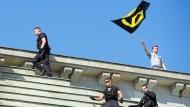 Nach den Demonstranten müssen auch Polizisten aufs Brandenburger Tor klettern, um das Denkmal wieder ansehnlich zu machen.