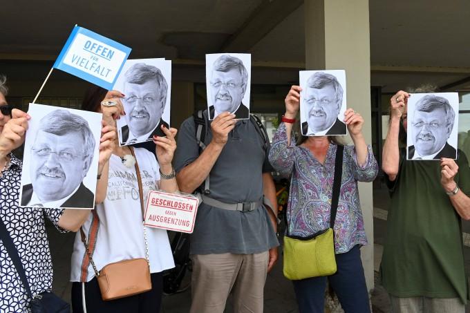 Demonstranten in Kassel halten sich Porträts des erschossenen Walter Lübckes, Regierungspräsidenten von Kassel, vor das Gesicht.