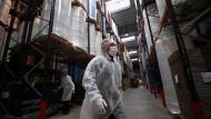 Ein Beispiel aus Frankreich: Dieser Mann arbeitet in Schutzkleidung in einem französischen Warenlager.
