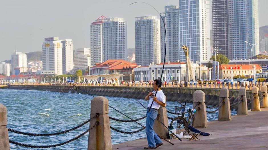 Ein Mann fischt am Rande der Skyline von Yantai.