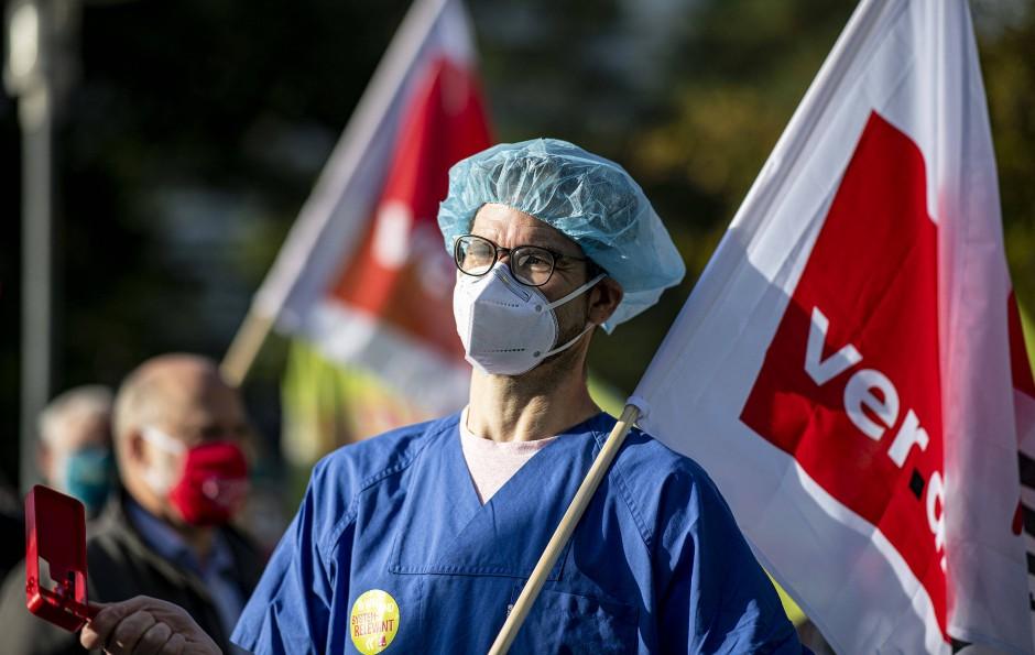 Für mehr Gehalt: Ein Arzt mit Mund-Nasen-Schutz und OP-Haube demonstriert in Potsdam.
