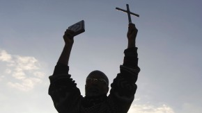 An anti-Mursi protester holds the Koran and a Cross as he shouts slogans against Egypt's President Mohamed Mursi and the Muslim Brotherhood on the Qasr El Nile bridge near Tahrir Square in Cairo