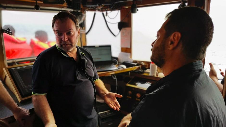 """Claus-Peter Reisch (links), der damalige Kapitän des Seenotrettungsschiffs """"Eleonore"""" der Hilfsorganisation Mission Lifeline, spricht im September 2019 mit italienischen Beamten."""