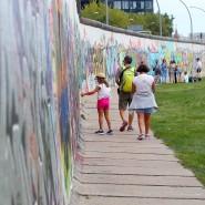 Am Gedenktag des Mauerbaus im Jahr 2019 gehen Menschen an einer Seite des längsten, noch erhaltenen Teilstücks der Berliner Mauer, der East Side Gallery, entlang.