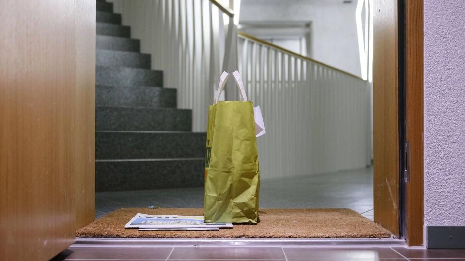 Eine Tüte mit Einkäufen und eine Zeitung für eine Familie in Quarantäne