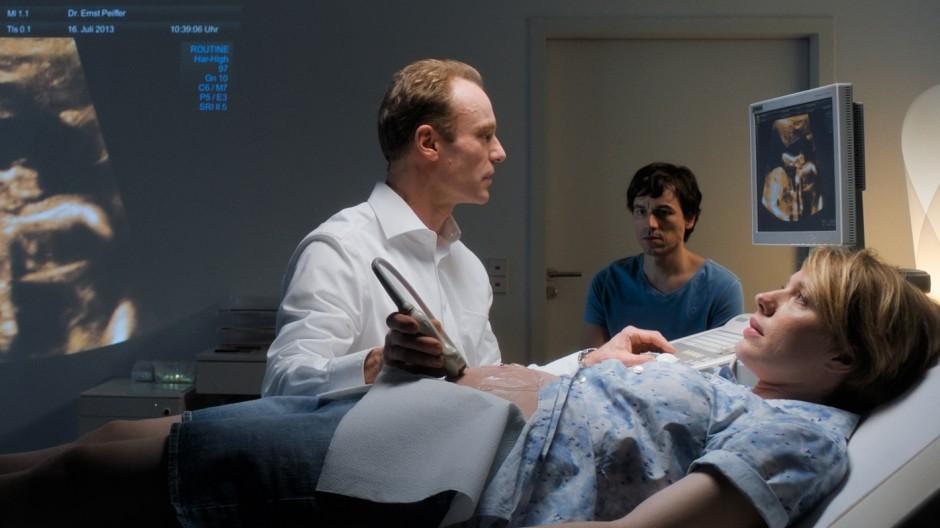 """Beim Ultraschall: Mark Waschke als Arzt, Anna Brüggemann als Dina und Alexander Khuon als Martin in dem Film """"Nö""""."""