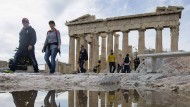 Tourists walk in front of the Parthenon Temple at the archaeological site of the Acropolis Hill in Athens