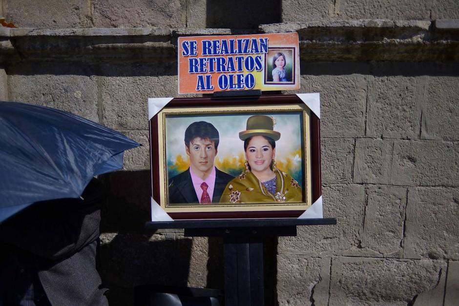 Ein Straßenkünstler stellt seine Ölbilder aus, auf denen Sylvester Stallone und eine Cholita zu sehen sind. Während des Preste-Fests porträtieren die Straßenkünstler oft die Organisatoren des Fests mit prominenten Persönlichkeiten wie Shakira, Jean Claude Van Damme oder sogar Osama Bin Laden.