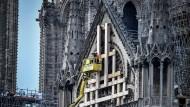 Arbeiter werden in einem Kran zur Rosette von Notre-Dame gebracht.